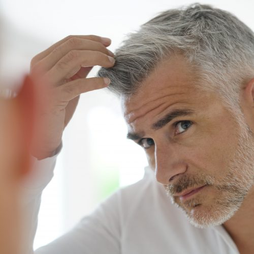 40-year-old man checking hair in front of mirror